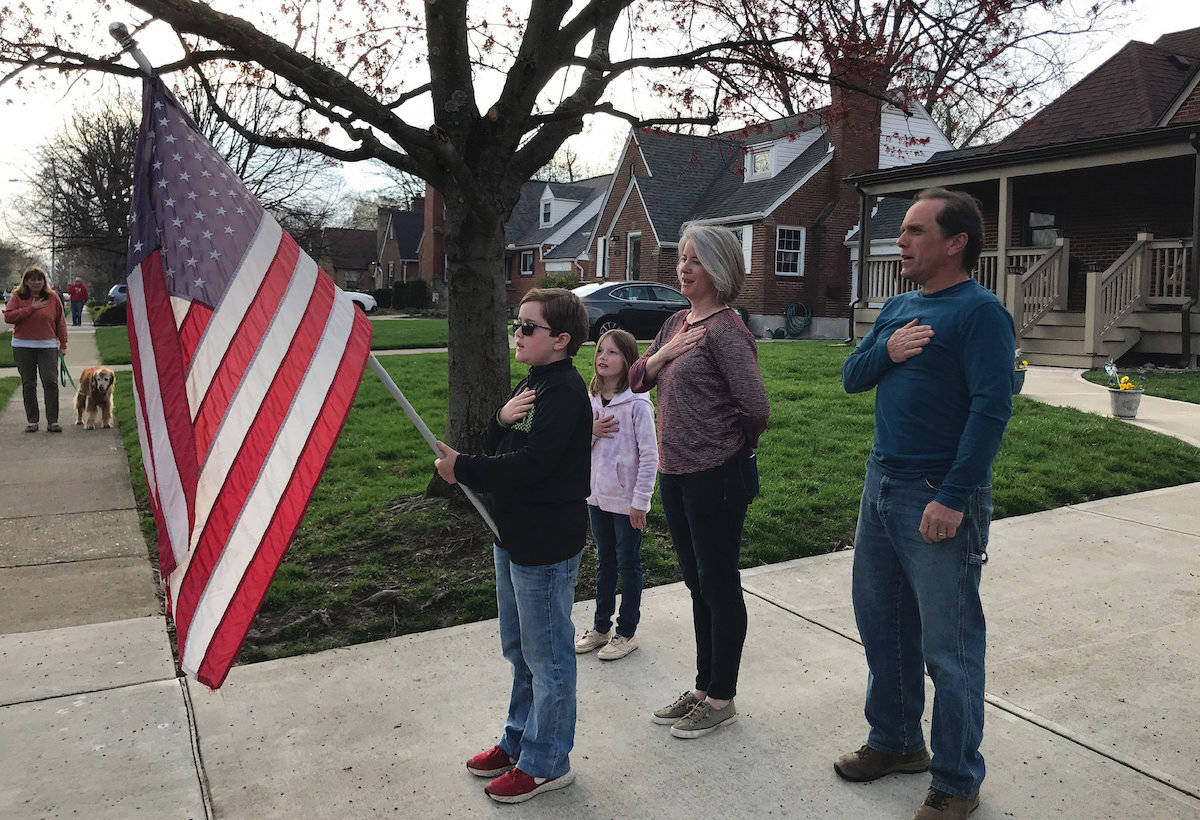 In this photo taken April 7, 2020, Zach Stamper holds the U.S. flag while his sister Juliette and parents Jennifer and Tim recite the Pledge of Allegiance in the driveway of their home, as next door neighbor, Ann Painter, left, participates in Kettering, Ohio. The Pledge has become a morning ritual in their neighborhood since schools closed due the COVID-19 threat. (AP Photo/Mitch Stacy)