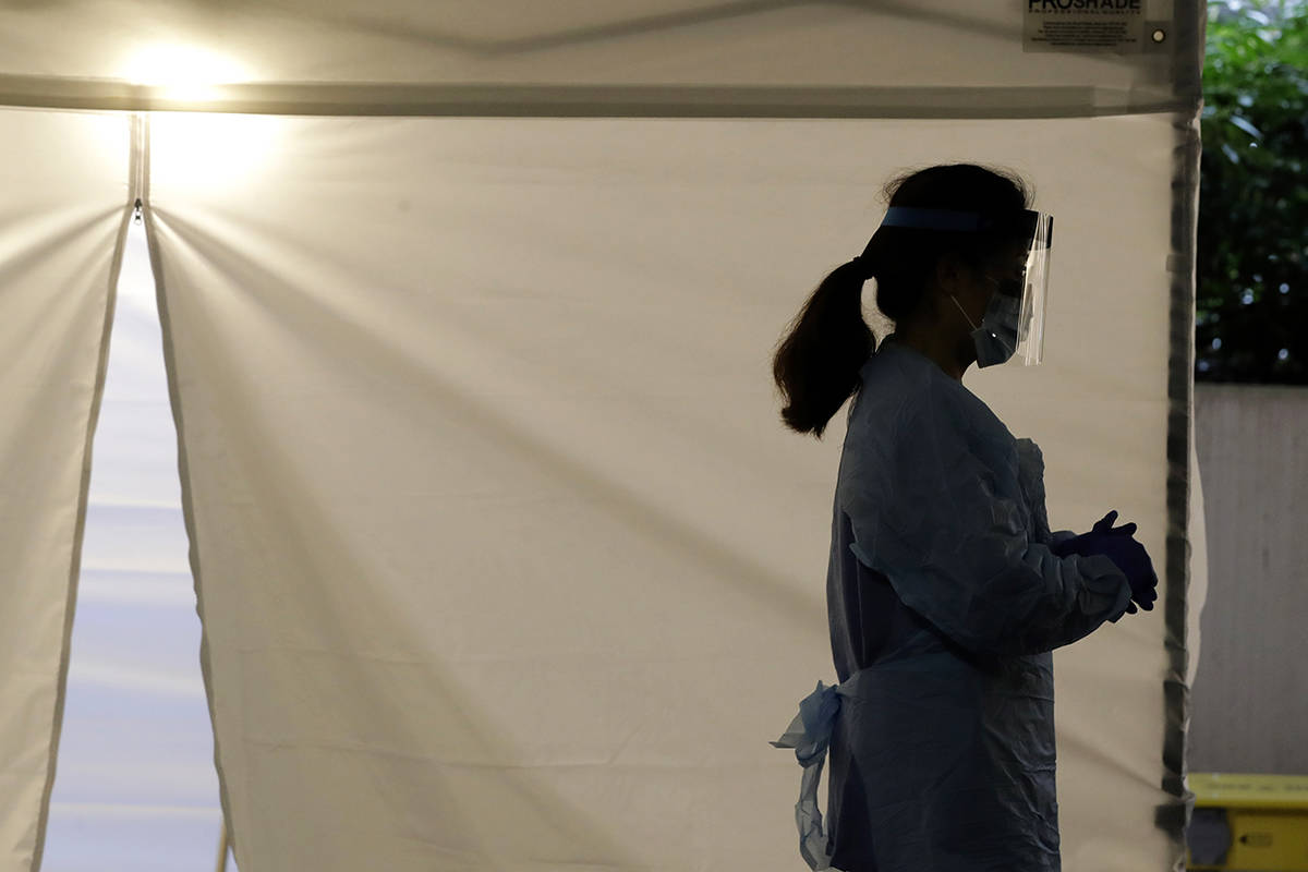 FILE - In this March 13, 2020 file photo, a nurse at a drive-up coronavirus testing station set up by the University of Washington Medical Center wears a face shield and other protective gear as she waits by a tent in Seattle. (AP Photo/Ted S. Warren, File)
