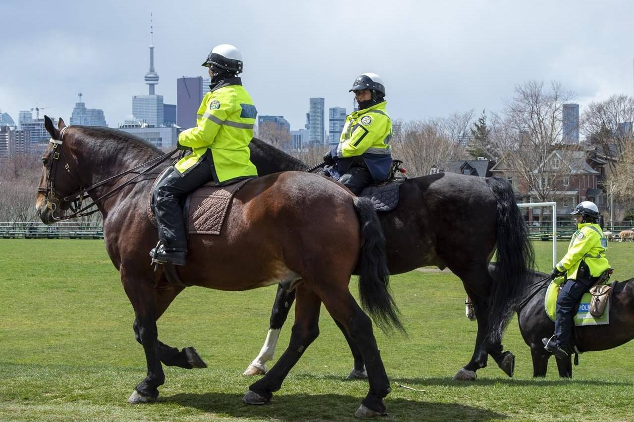 Toronto Police Mounted Unit officers patrol a city park in Toronto on Thursday, April 16, 2020. The Canadian Civil Liberties Association says it's going to seek amnesty for all tickets issued for municipal recreational infractions during the COVID-19 pandemic. THE CANADIAN PRESS/Frank Gunn