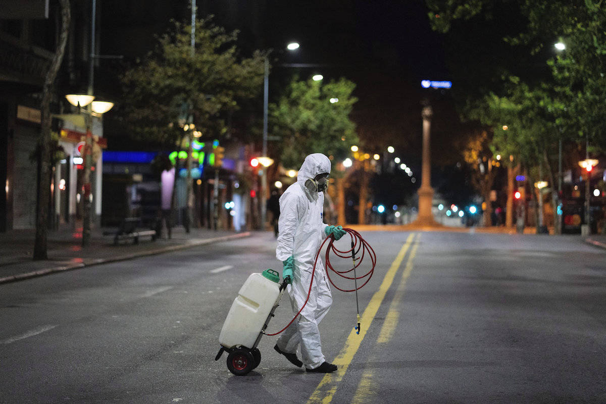 A city worker crosses a main avenue to disinfect a bus stop amid the spread of new coronavirus in Montevideo, Uruguay, early Monday, April 20, 2020. (AP Photo/Matilde Campodonico)