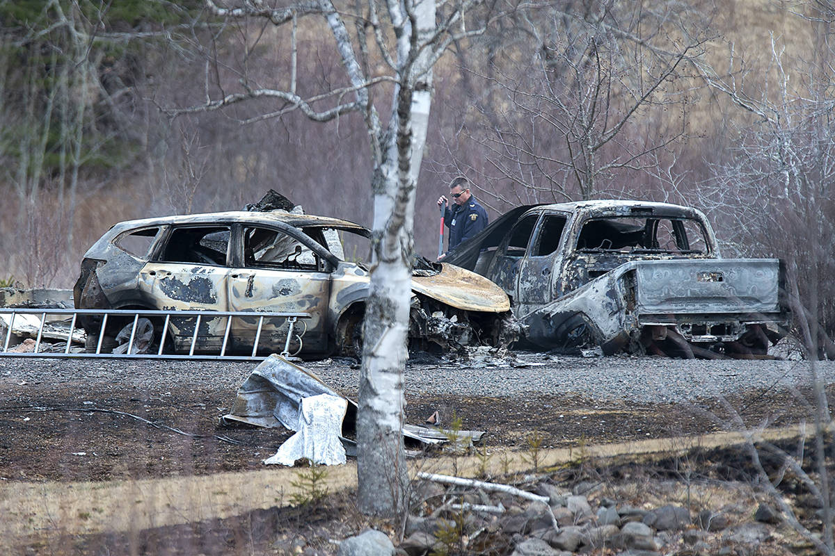 An RCMP investigator inspects vehicles destroyed by fire at the residence of Alanna Jenkins and Sean McLean, both corrections officers, in Wentworth Centre, N.S. on Monday, April 20, 2020. A neighbour, Tom Bagley, was also killed on the property. Police say at least 19 people are dead, including RCMP Const. Heidi Stevenson, after a man, driving a restored police car, went on a murder spree in several Nova Scotia communities. The alleged killer, 51, was shot and killed by police. THE CANADIAN PRESS/Andrew Vaughan