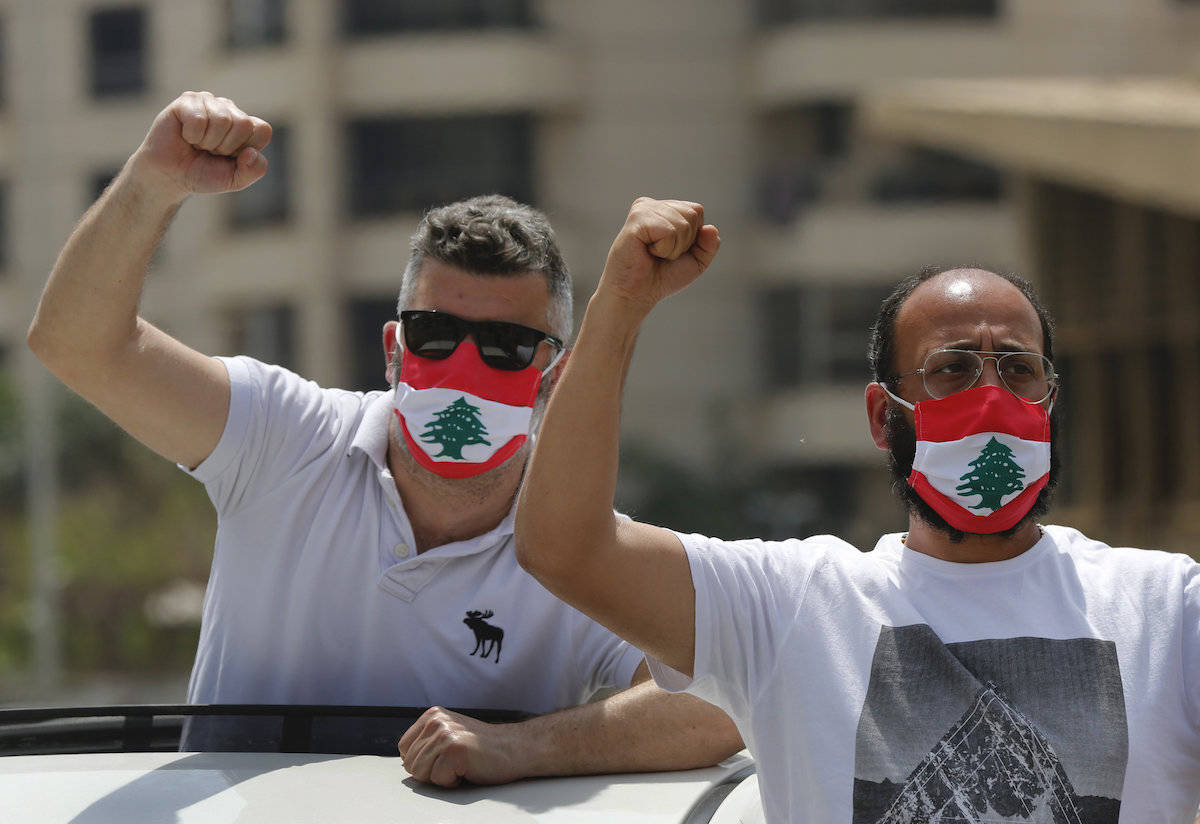 Anti-government protesters shout slogans, while wearing masks with the colors of the Lebanese flag to help curb the spread of the coronavirus, during a driving convoy protest through the streets to express rejection of the political leadership they blame for the economic and financial crisis, in Beirut, Lebanon, Tuesday, April 21, 2020. Lebanon's parliament began Tuesday a three-day legislative session at a Beirut theater so that legislators can observe coronavirus social distancing measures, as protests against the country's ruling elite in the crisis-hit country resumed. (AP Photo/Hussein Malla)