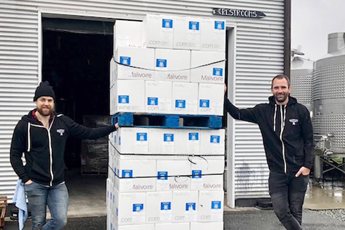 Backyard Vineyard winemaker Liam Berti and cellar hand Riivo Vahk with the 2,000 bottles of hand sanitizer the winery made to deliver to local hospitals and doctors. (Backyard Vineyard photo)