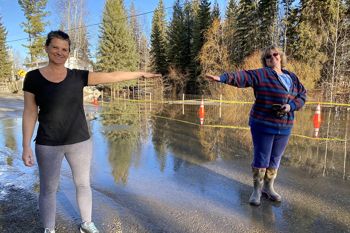 Wildwood neighbours Cheryl Michalchuk and Marion Bremner social distance while getting to know each other better in the face of spring flooding. (Angie Mindus photo - Williams Lake Tribune)