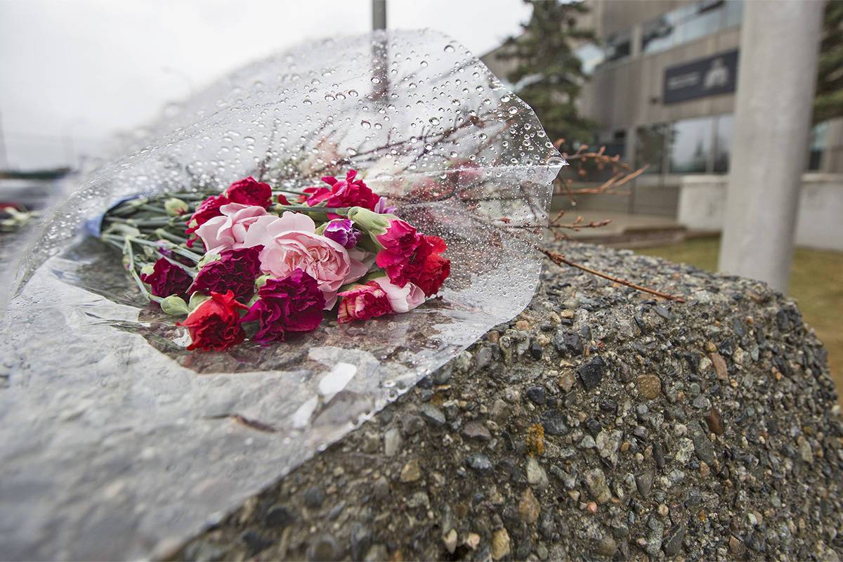 Flowers lay in the rain below half mast flags at the RCMP headquarters in Whitehorse on April 23, in honour of the officer killed on April 19 in Nova Scotia. (Crystal Schick/Yukon News)