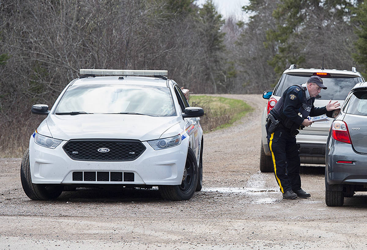 An RCMP officer talks with a local resident before escorting them home at a roadblock in Portapique, N.S. on Wednesday, April 22, 2020. RCMP say at least 22 people are dead after a man who at one point wore a police uniform and drove a mock-up cruiser, went on a murder rampage in Portapique and several other Nova Scotia communities. THE CANADIAN PRESS/Andrew Vaughan
