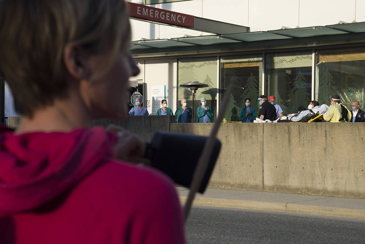 A woman hits a cow bell with a drum stick as a part of the 7pm tribute to health-care workers outside the Lions Gate Hospital in North Vancouver, B.C. Wednesday, April 8, 2020. THE CANADIAN PRESS/Jonathan Hayward