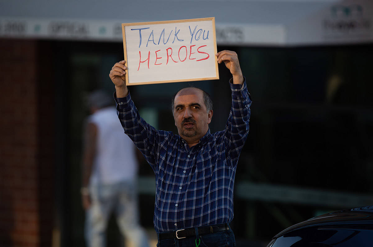 A man holds up a sign across the street from Royal Columbian Hospital, in support of health care workers treating those affected by COVID-19, in New Westminster, B.C., on Thursday, April 16, 2020. THE CANADIAN PRESS/Darryl Dyck