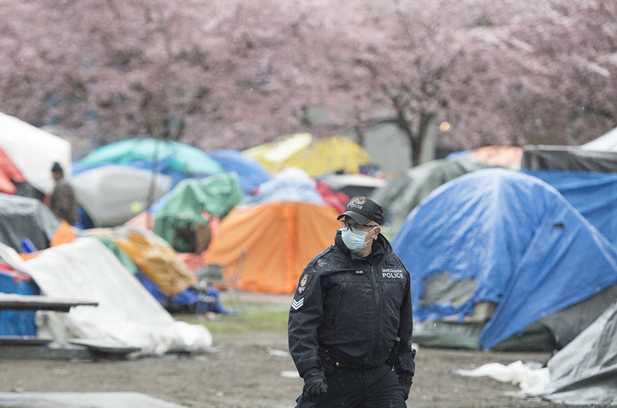 A Vancouver Police officer is seen at Oppenheimer Park in Vancouver's Downtown Eastside Thursday, March 26, 2020. THE CANADIAN PRESS/Jonathan Hayward