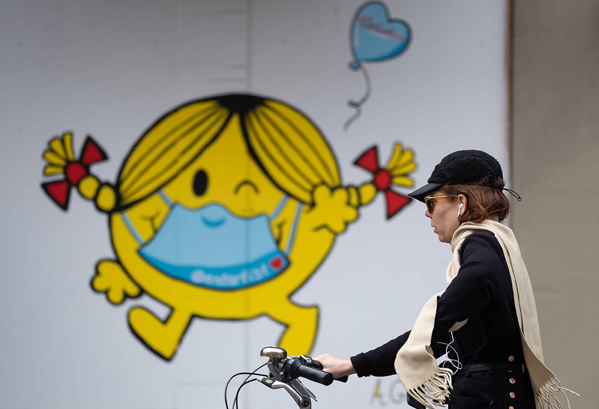 A woman rides a bike past artwork of author and illustrator Roger Hargreaves' 'Little Miss Sunshine' character wearing a face mask, painted on the outside of a boarded up business in downtown Vancouver, on Sunday, April 19, 2020. THE CANADIAN PRESS/Darryl Dyck
