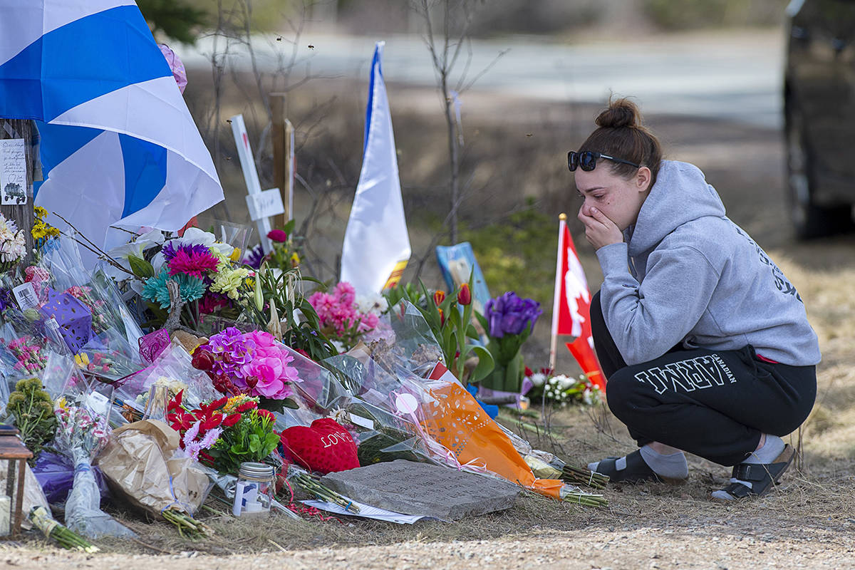 A woman pays her respects at a roadside memorial on Portapique Road in Portapique, N.S. on Friday, April 24, 2020. At least 22 people are dead after a man, who at one point wore a police uniform and drove a mock-up cruiser, went on a murder rampage in Portapique and several other Nova Scotia communities. THE CANADIAN PRESS/Andrew Vaughan