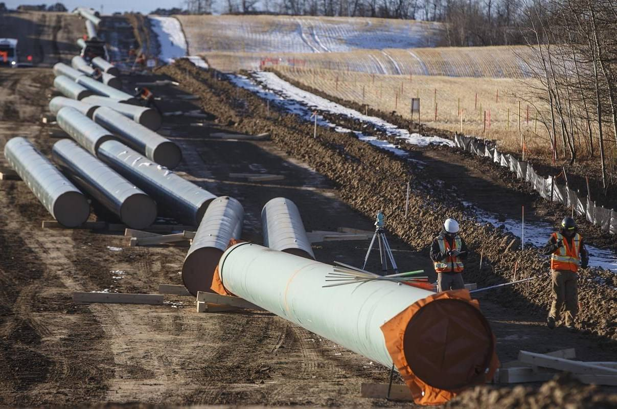 Workers survey around pipe to start of right-of-way construction for the Trans Mountain Expansion Project, in Acheson, Alta., Tuesday, Dec. 3, 2019. Energy projects like an LNG Canada export terminal and the Trans Mountain pipeline expansion may face short-term setbacks but the pandemic and oil price crash shouldn't threaten their long-term viability, economists say. THE CANADIAN PRESS/Jason Franson