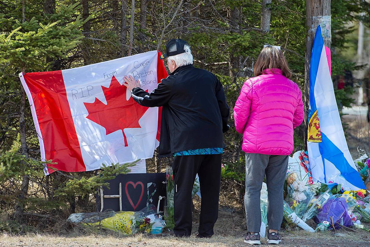 A couple place a flag at a memorial in Portapique, N.S. on Wednesday, April 22, 2020. RCMP say at least 22 people are dead after a man who at one point wore a police uniform and drove a mock-up cruiser, went on a murder rampage in Portapique and several other Nova Scotia communities. THE CANADIAN PRESS/Andrew Vaughan