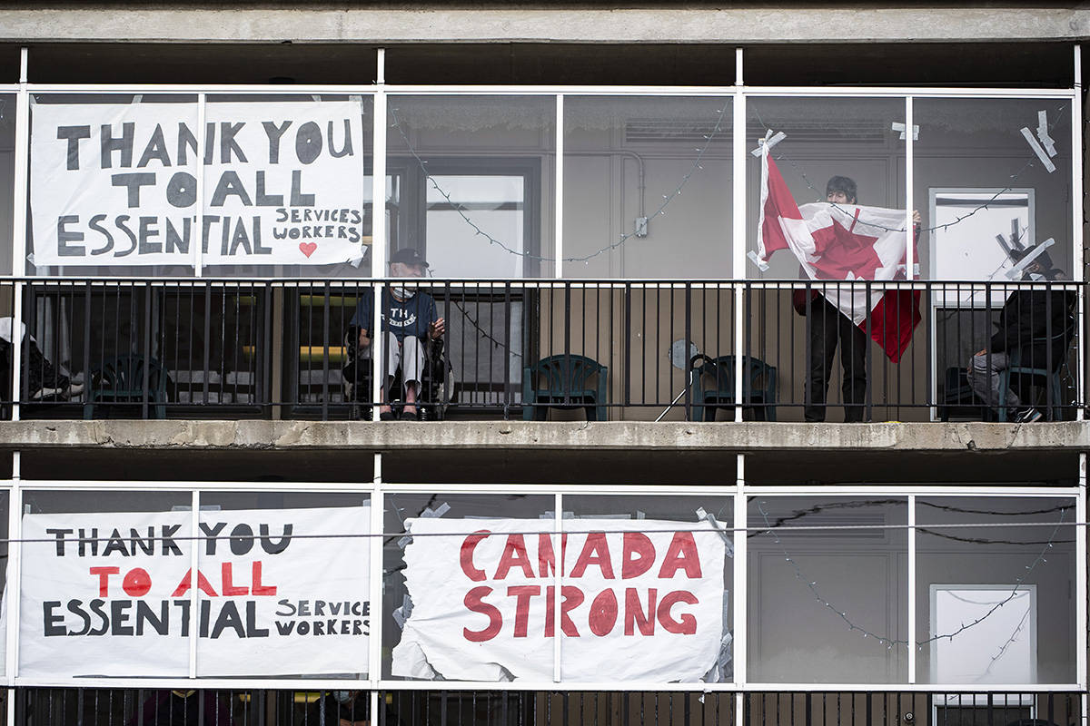 A resident untangles a Canadian flag in order to tape it back up to the window on a balcony at the Laurier Manor in Ottawa, a long term care facility experiencing an outbreak of COVID-19, on Sunday, April 26, 2020. THE CANADIAN PRESS/Justin Tang