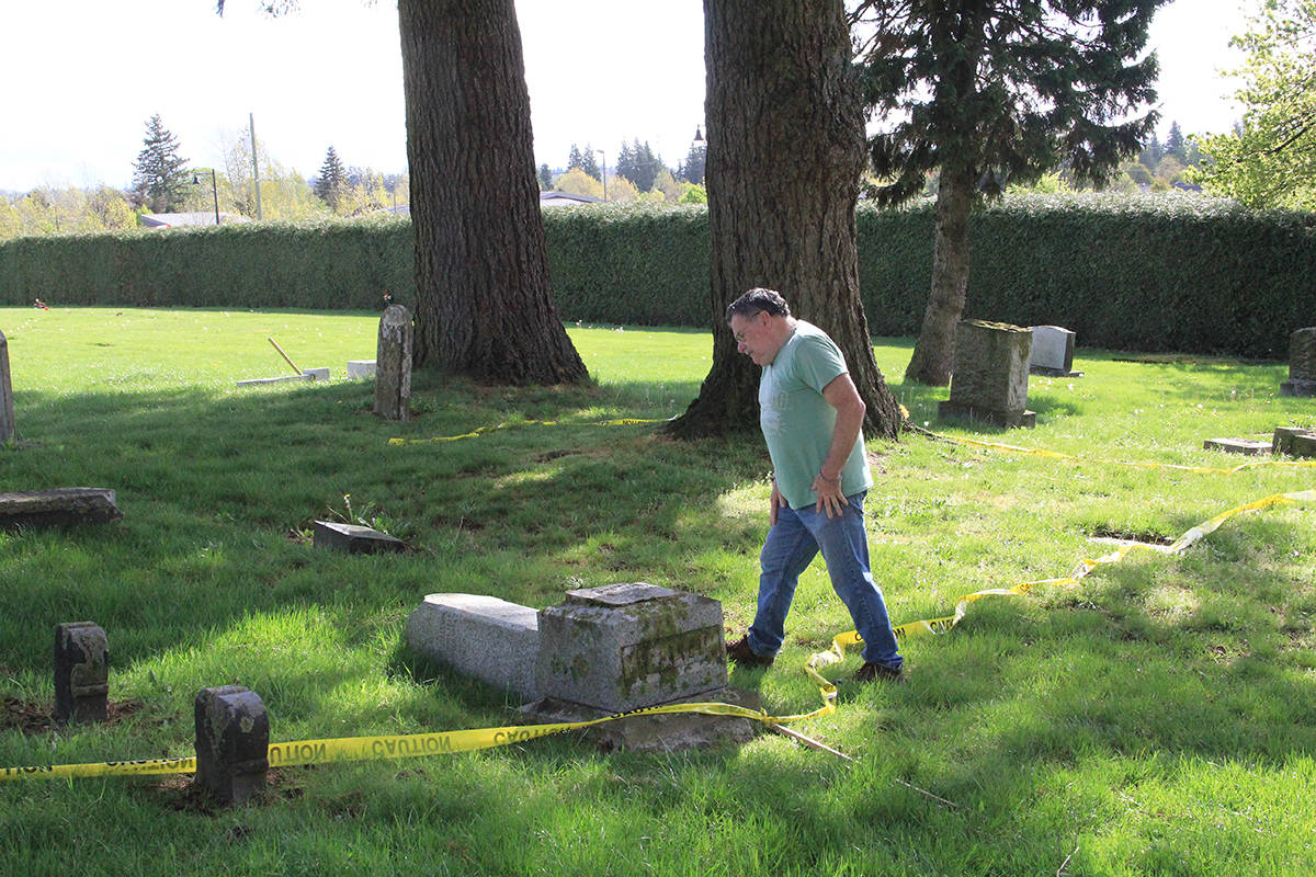 Michael Gibbs, president of the Surrey Historical Society, inspects vandalized grave markers in the Surrey Centre Cemetery April 27. Gibbs wondered if it might be time to install security cameras in the 139-year-old cemetery. (Photo: Malin Jordan)