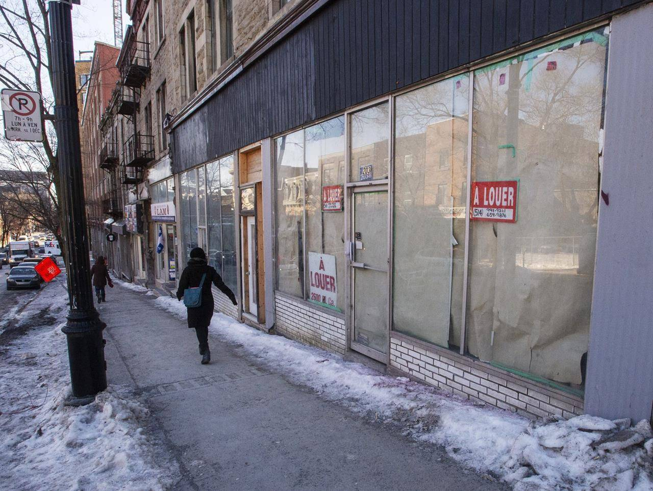 A pedestrian walks past an empty store front in Montreal, Wednesday, Jan. 29, 2020. THE CANADIAN PRESS/Ryan Remiorz