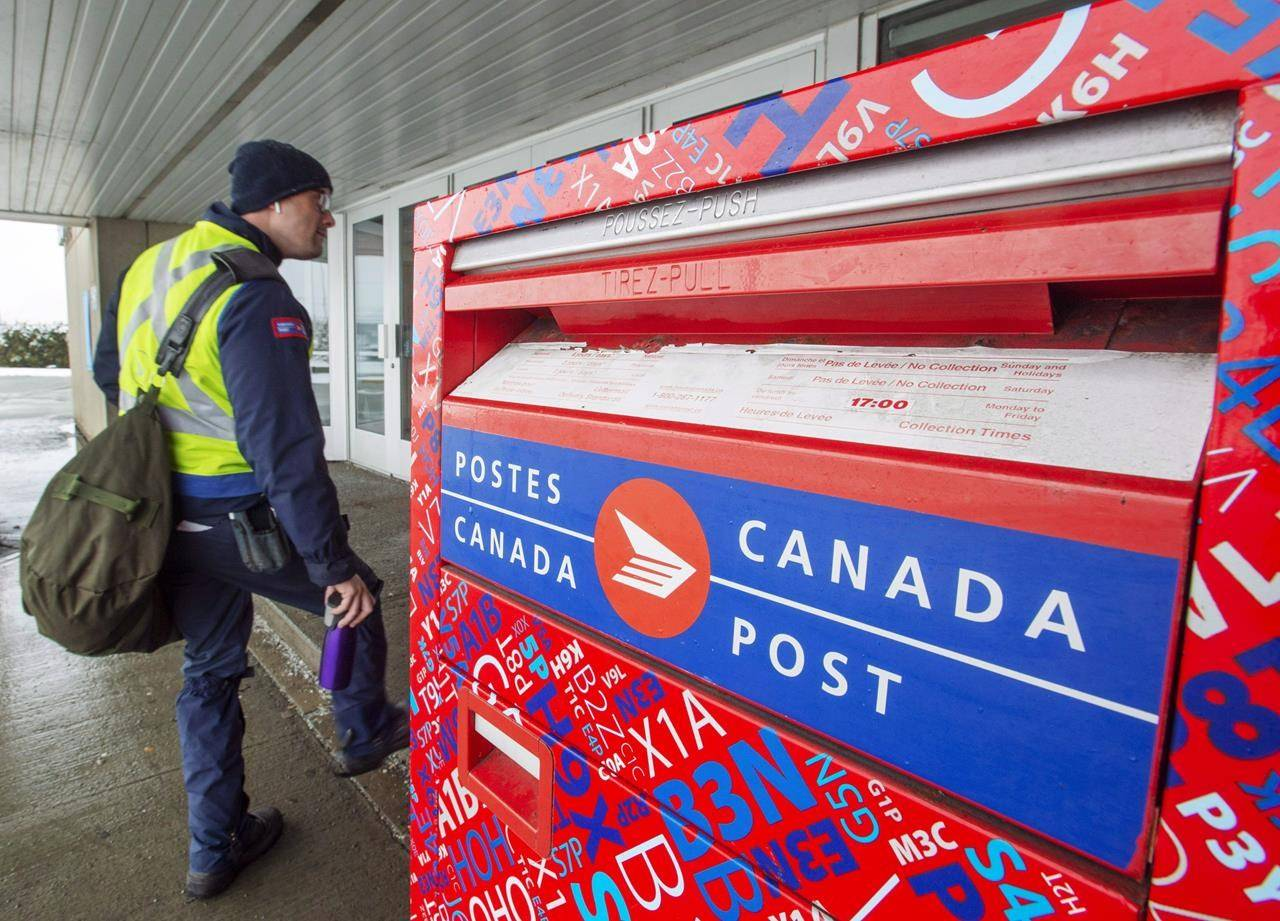 A Canada Post worker. Locally, Canada Post is asking for people to keep their dogs inside during mail delivery. THE CANADIAN PRESS/Ryan Remiorz