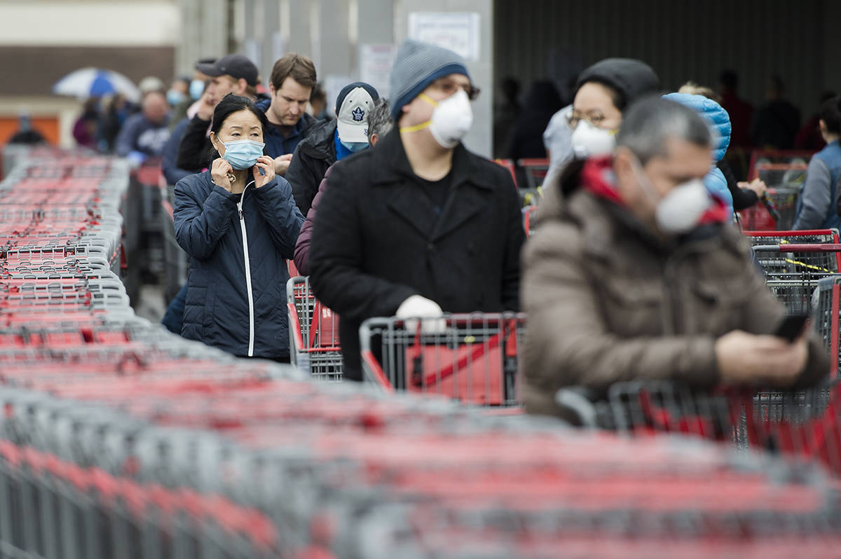 Hundreds of people wait in line to enter Costco in Toronto on Monday, April 13. Canadian Costco stores are not requiring shoppers to wear face masks in response to the COVID-19 pandemic, despite changes in policy south of the border. (THE CANADIAN PRESS/Nathan Denette)