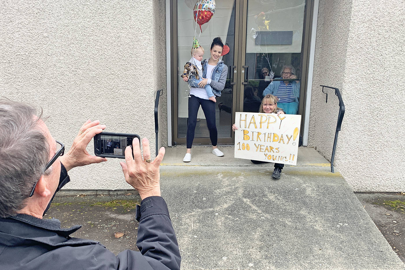 Cameron Mcdonald takes a photo of Joanne Matthews, her daughter Amanda Venhaus and Amanda's baby Nixon from Abbotsford with Dorothy Dewar inside. All are family members of Dorothy who turned 100 on April 30, 2020. (Paul Henderson/ The Progress)