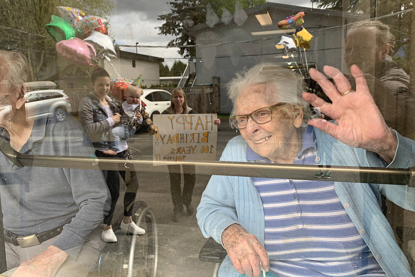 Dorothy Dewar, who turned 100 on April 30, 2020, waves to family members who came to see her at Eden Care Centre in Chilliwack to sing Happy Birthday. (Paul Henderson/ The Progress)