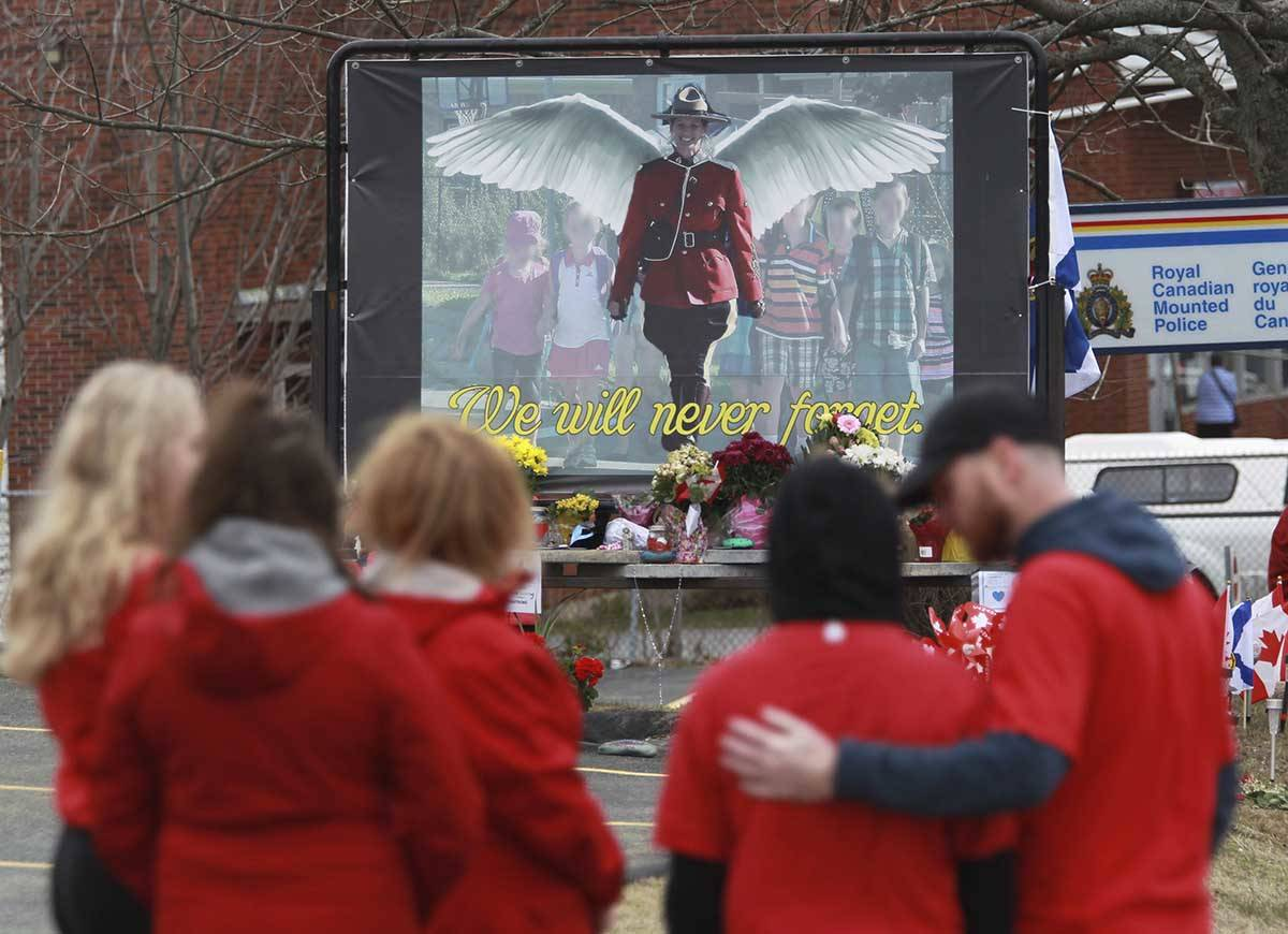 Mourners, asked to wear red on Friday, are seen near a mural dedicated to slain Royal Canadian Mounted Police Const. Heidi Stevenson, during a province-wide, two-minutes of silence for the 22 victims of last weekend's shooting rampage, in front of the RCMP detachment in Cole Harbour, Nova Scotia, Friday, April 24, 2020. (Tim Krochak/The Canadian Press via AP)                                Mourners, asked to wear red on Friday, are seen near a mural dedicated to slain Royal Canadian Mounted Police Const. Heidi Stevenson, during a province-wide, two-minutes of silence for the 22 victims of last weekend's shooting rampage, in front of the RCMP detachment in Cole Harbour, Nova Scotia, Friday, April 24, 2020. (Tim Krochak/The Canadian Press via AP)