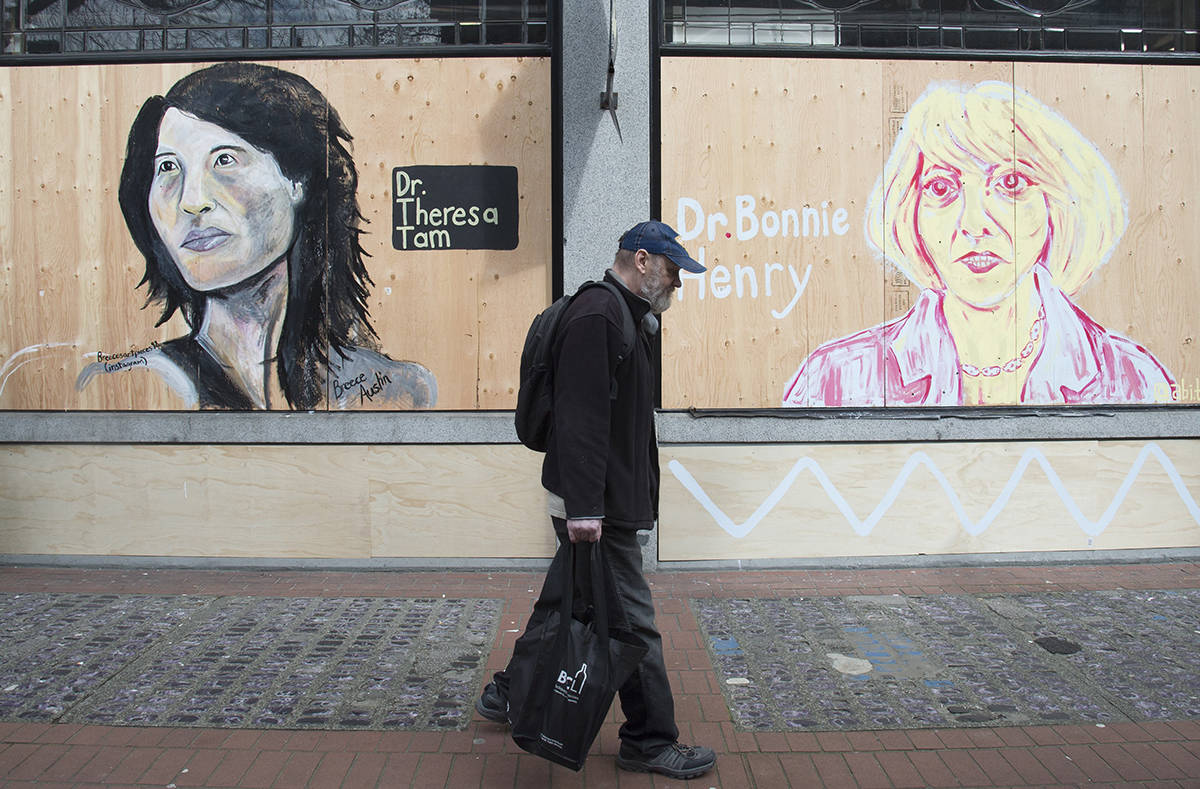 A man walks past portraits of Dr. Theresa Tam and Dr. Bonnie Henry on a boarded up business in downtown Vancouver, B.C. Wednesday, April 1, 2020. THE CANADIAN PRESS/Jonathan Hayward
