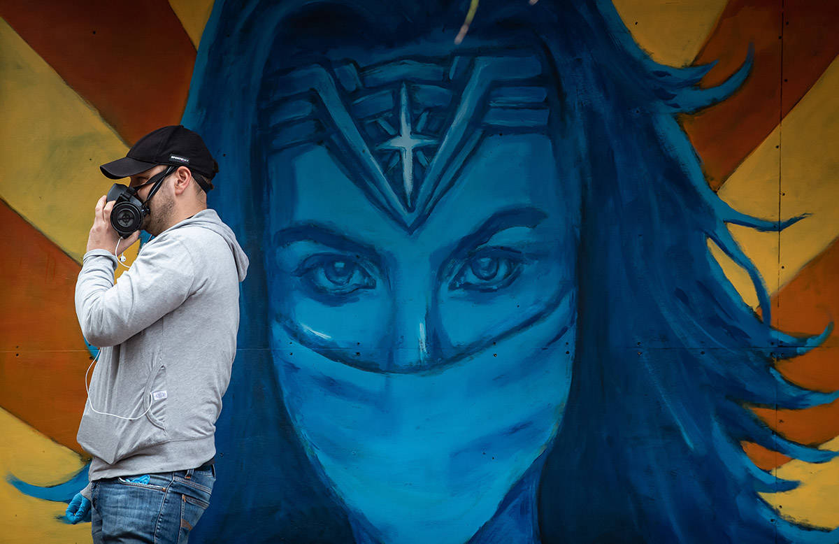Artist Lukas Lundberg pauses to talk to a passerby while working on a painting of Wonder Woman depicted as a doctor on the boarded up windows of a closed Gastown business, in Vancouver, on Sunday, April 26, 2020. THE CANADIAN PRESS/Darryl Dyck