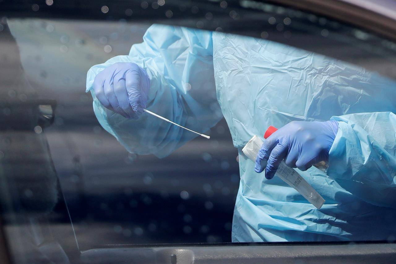 A medical assistant prepares to take a swab from a patient at a new drive-thru and walk-up coronavirus testing site in Seattle, Saturday, April 25, 2020. THE CANADIAN PRESS/AP-Elaine Thompson
