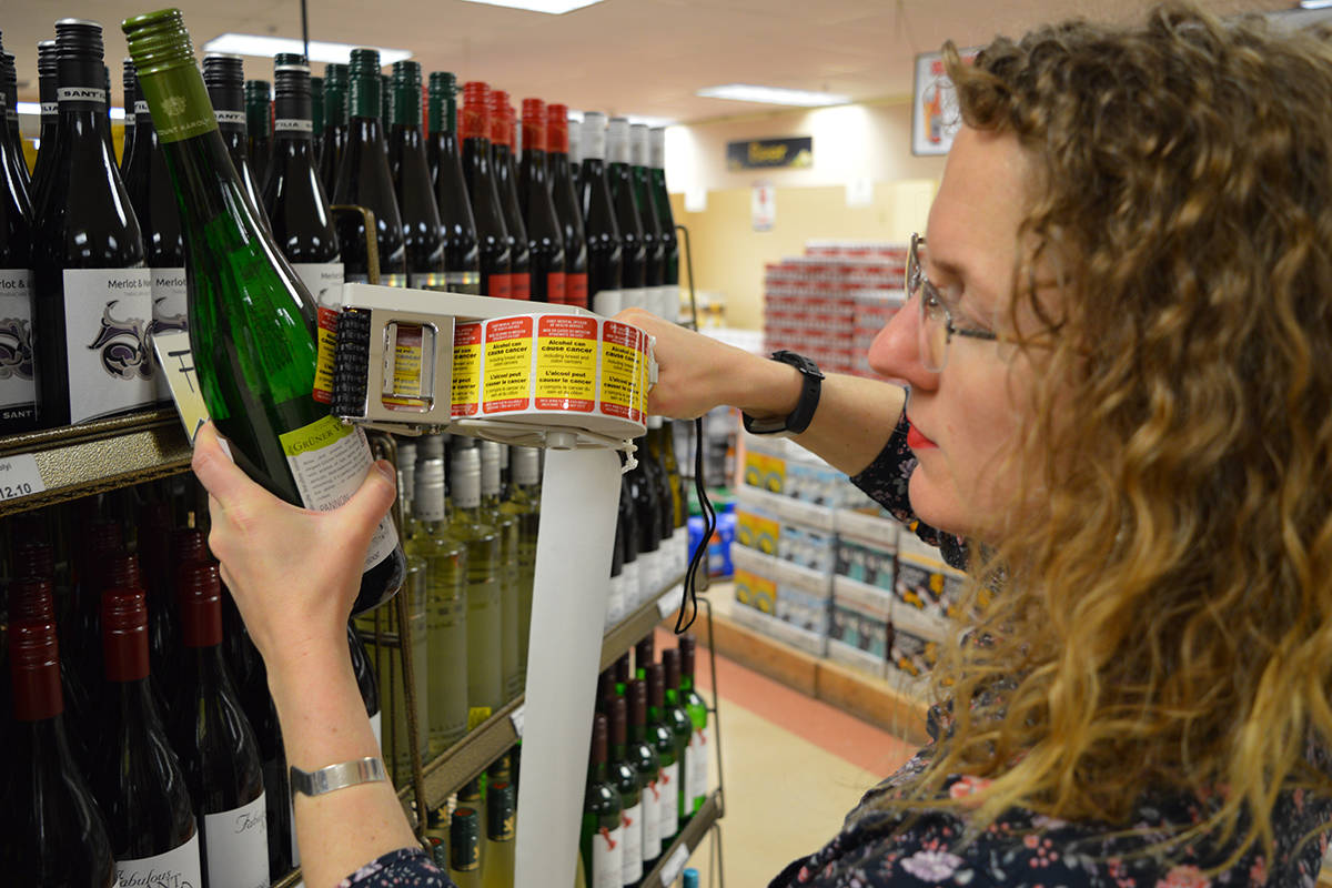 Kate Vallance, CISUR research associate and lead author on an evaluation of baseline survey data, places stickers on alcohol containers in a Yukon liquor store. (Provided by the University of Victoria)