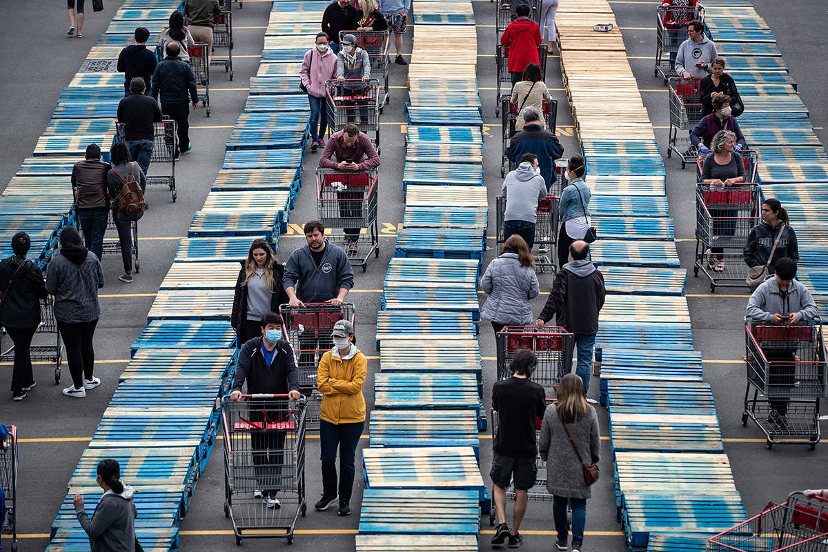 Shoppers are separated by rows of wood pallets to help with physical distancing as they line up to enter a Costco store in Burnaby, B.C., on Sunday, April 19, 2020. THE CANADIAN PRESS/Darryl Dyck
