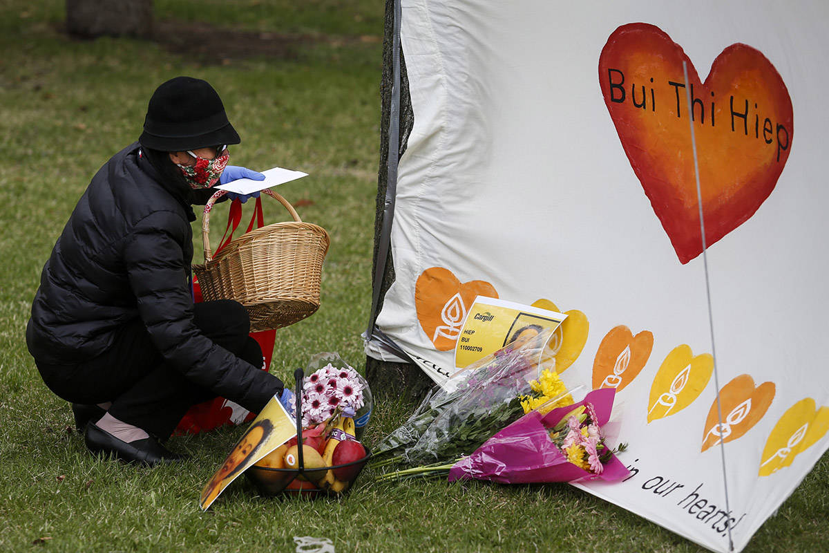 A mourner places flowers at a memorial for Hiep Bui Nguyen, a Cargill worker who died from COVID-19, in Calgary, Alta., Monday, May 4, 2020, amid a worldwide COVID-19 pandemic. THE CANADIAN PRESS/Jeff McIntosh