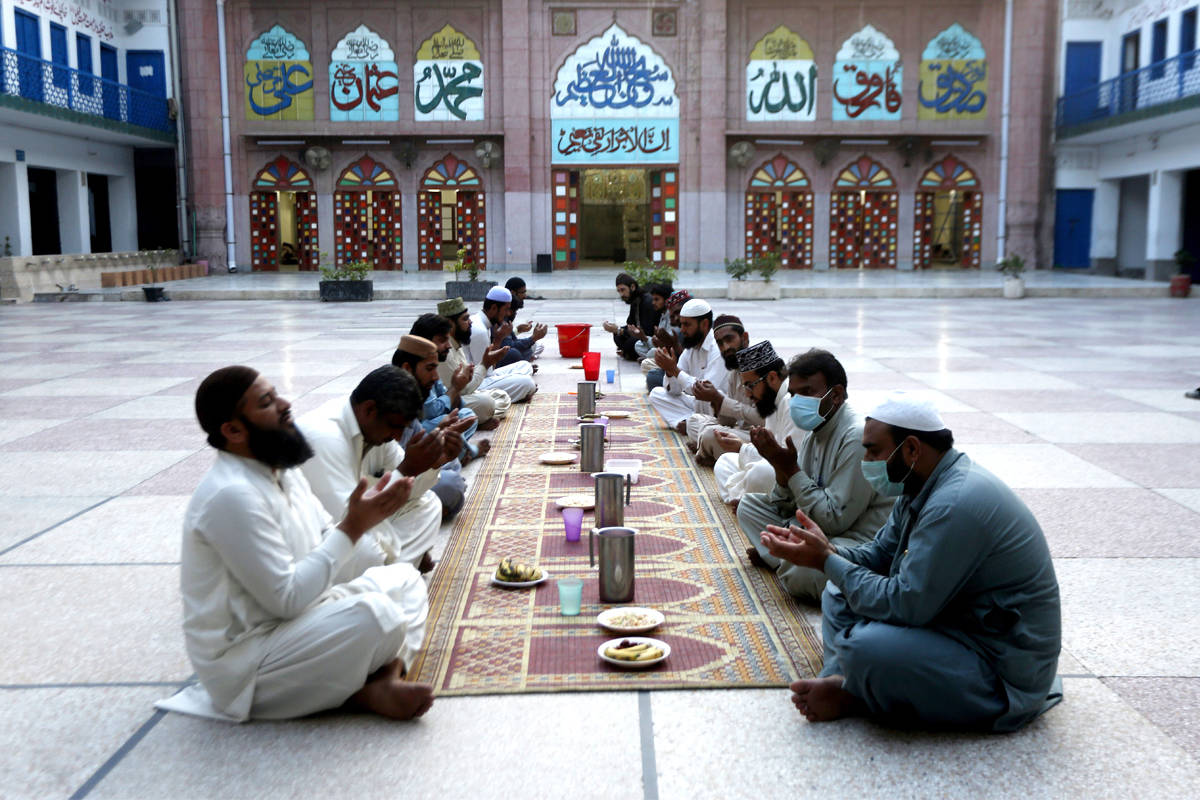 People pray before breaking their fast in the Muslim fasting month of Ramadan, during a government-imposed nationwide lockdown to help contain the spread of the coronavirus, in Lahore, Pakistan. Muslims across the world are observing Ramadan when the faithful refrain from eating, drinking and smoking from dawn to dusk. Photo: K.M. Chaudhry/Associated Press