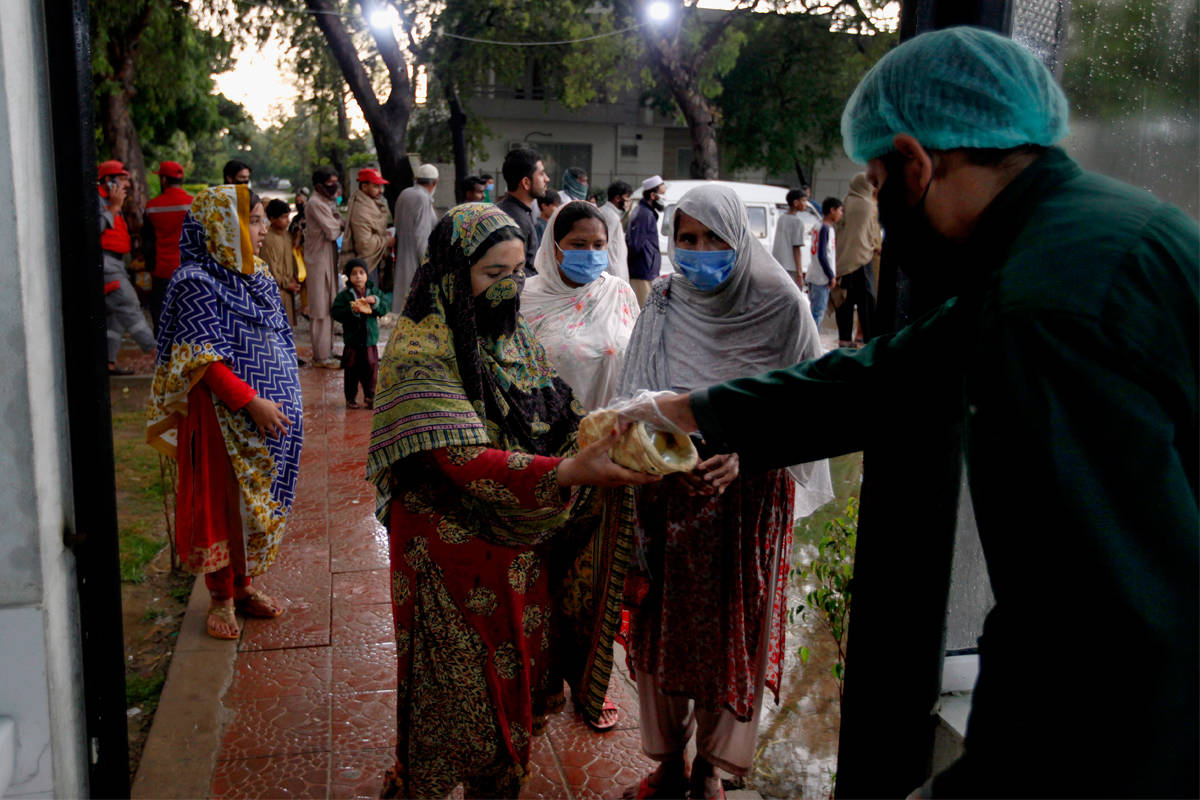 A worker from Saylani Welfare Trust gives free food to women for breaking their fast on the first day of Ramadan, in Islamabad, Pakistan. Photo: Anjum Naveed/Associated Press