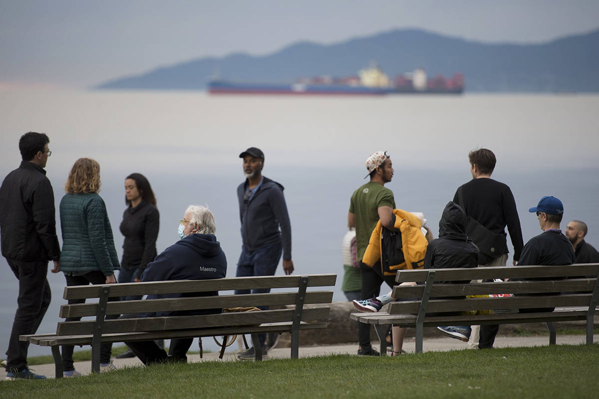 People are seen walking along the seawall in English Bay in Vancouver, Monday, May 4, 2020. THE CANADIAN PRESS/Jonathan Hayward