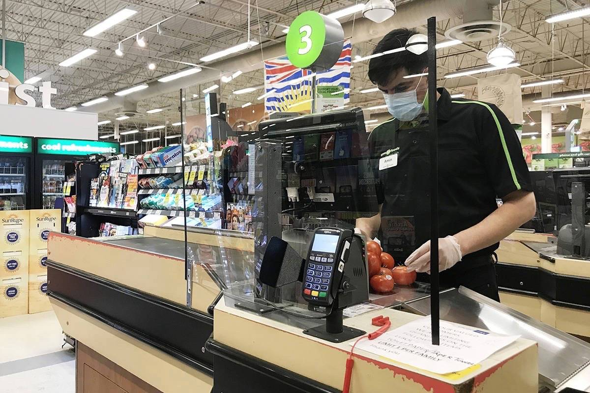 Barrier protects checkout clerk at a grocery store in North Vancouver, March 22, 2020. Other businesses are expected to use similar strategies to minimize risk to customers and employees. (The Canadian Press)