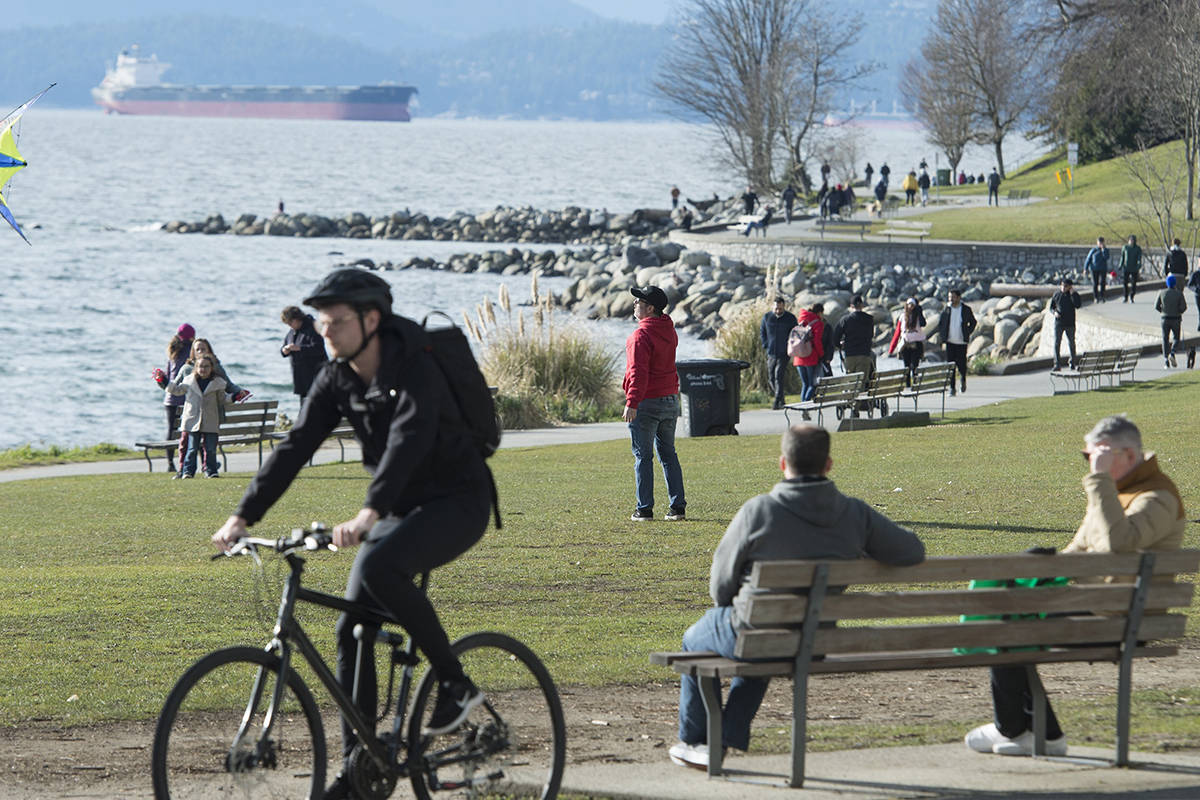 People walk, sit on benches, bike, fly kites along the seawall in English Bay in Vancouver, B.C. Tuesday, March 24, 2020. THE CANADIAN PRESS/Jonathan Hayward