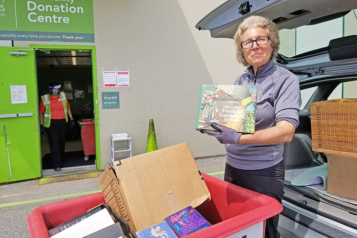 Julie Stanton shows off some of the books she dropped off at the Langley Value Village thrift store on Wednesday, May 6th. After a six-week shutdown, the store reopened on Tuesday, generating line-up of people waiting to drop off donations. Stanton drove in from North Vancouver to help a friend in Langley who had been stockpiling donations for when the store reopened. (Dan Ferguson/Langley Advance Times)