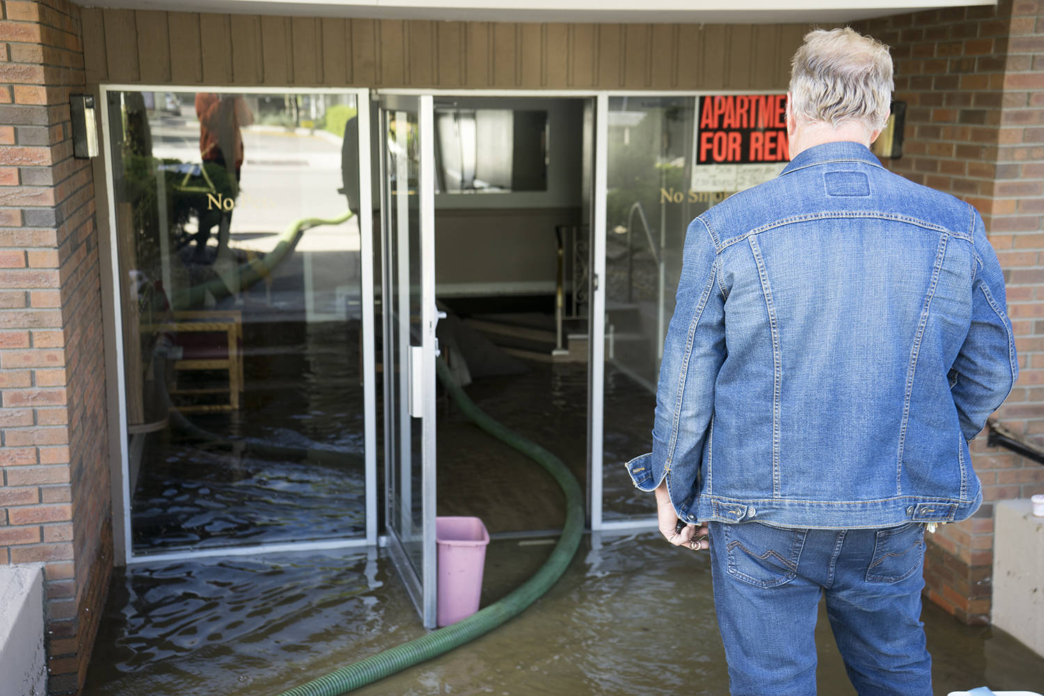 A resident of an apartment building on Rowcliffe Avenue looks over the flooded entryway of his building on May 7, 2020. (Michael Rodriguez - Kelowna Capital News)
