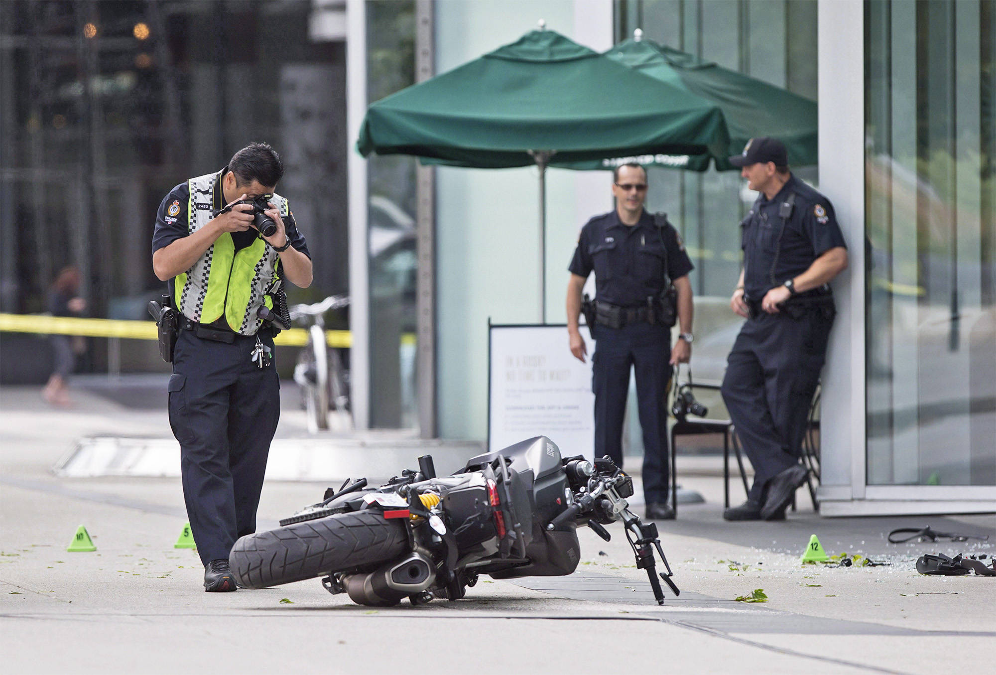 """A police officer photographs a motorcycle after a female stunt driver working on the movie """"Deadpool 2"""" died after a crash on set, in Vancouver, B.C., on Monday August 14, 2017. British Columbia's workplace safety agency says multiple failures of a production company contributed to the death of a stunt performer on the set of """"Deadpool 2.†THE CANADIAN PRESS/Darryl Dyck"""