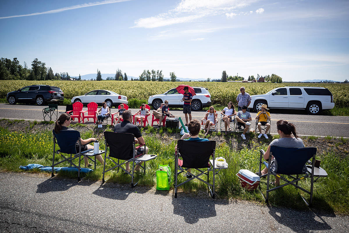 Three generations of the Nunnikhoven family including those who live in Lynden, Wash., back, and those who live in Aldergrove, B.C., front, spend Mother's Day together separated by a ditch along the Canada-U.S. border, in Aldergrove, B.C., on Sunday, May 10, 2020. The stretch of international border approximately an hour southeast of Vancouver has become a popular meeting spot for families and loved ones separated due to the closure of the Canada-U.S. border to non-essential travel due to COVID-19. THE CANADIAN PRESS/Darryl Dyck