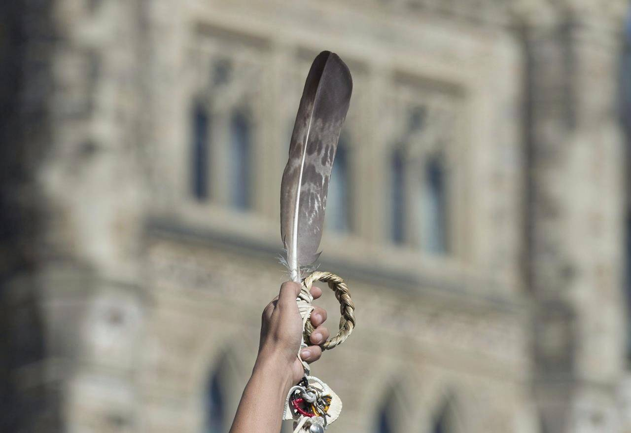 FILE – An eagle feather is held up during a rally for Missing and Murdered Indigenous Women and Girls on Parliament Hill in Ottawa on October 4, 2016. With reports of a sharp rise in violence against Indigenous women as COVID-19 restrictions keep families stuck in their homes, concerns are being raised about whether the pandemic could delay the promised June delivery of a national action plan on missing and murdered Indigenous women. THE CANADIAN PRESS/Adrian Wyld