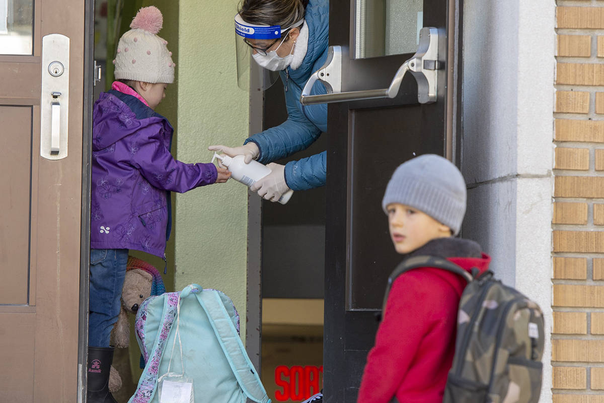Students get their hands sanitized as they enter Ecole Marie Rose as elementary schools outside the greater Montreal area reopen Monday May 11, 2020 in Saint Sauveur, Que.. Schools and daycare centers have been closed due to the COVID-19 pandemic. THE CANADIAN PRESS/Ryan Remiorz