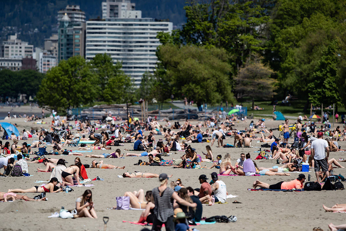 People sun themselves at Kitsilano Beach as temperatures reached highs into the 20s according to Environment Canada, in Vancouver, on Saturday, May 9, 2020. THE CANADIAN PRESS/Darryl Dyck