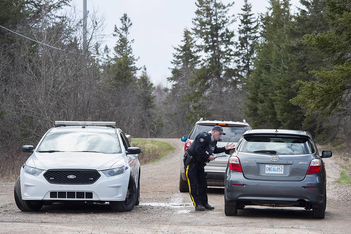 An RCMP officer talks with a local resident before escorting them home at a roadblock in Portapique, N.S. on Wednesday, April 22, 2020. THE CANADIAN PRESS/Andrew Vaughan