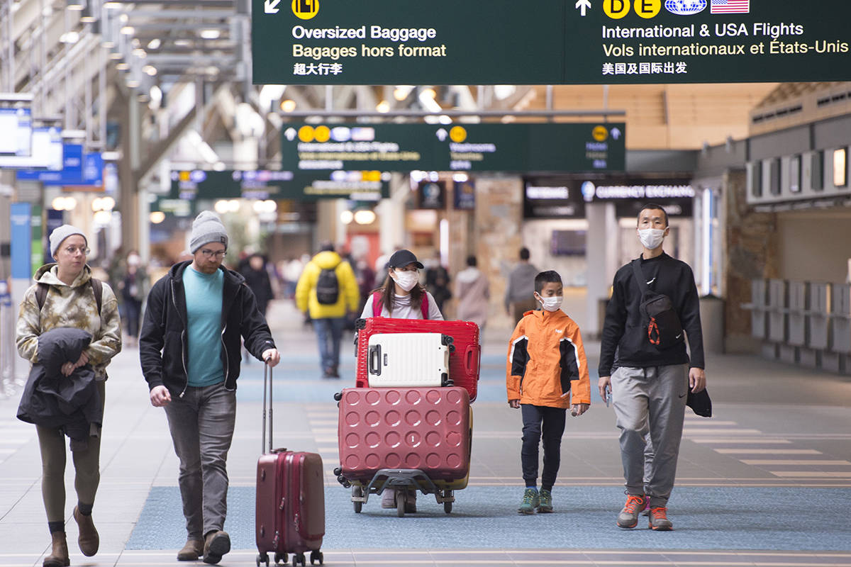 Travellers are seen at Vancouver International Airport in Richmond, B.C. Friday, March 13, 2020. THE CANADIAN PRESS/Jonathan Hayward