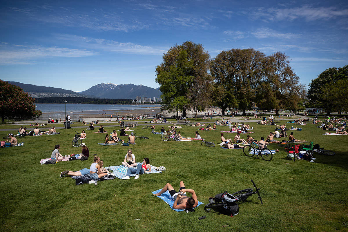 People sit and lie in the sun at Kitsilano Beach Park as temperatures reached highs into 20s according to Environment Canada, in Vancouver, on Saturday, May 9, 2020. THE CANADIAN PRESS/Darryl Dyck