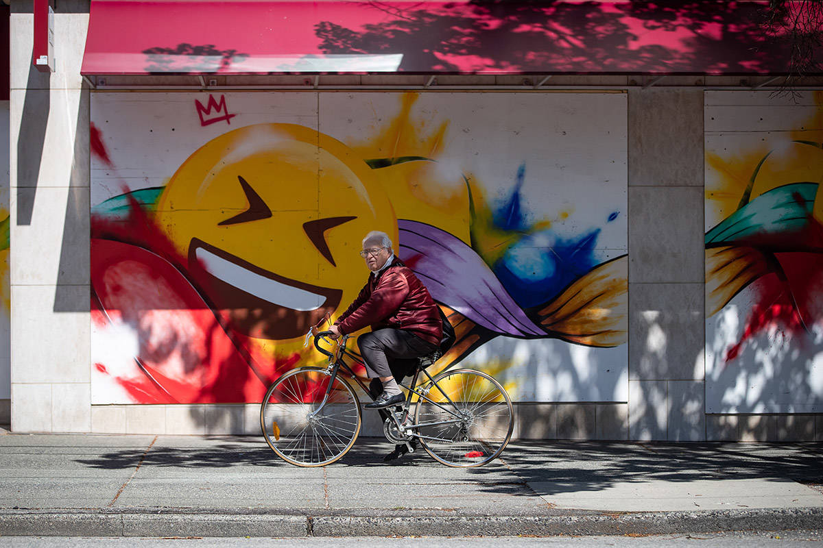 A man rides a bike past a large emoji face painted on the boarded up windows of a store on Robson Street, in Vancouver, on Wednesday, May 6, 2020. British Columbia has outlined a gradual reopening of its economy with certain health services, retail outlets, restaurants, salons and museums resuming some operations in mid-May. THE CANADIAN PRESS/Darryl Dyck