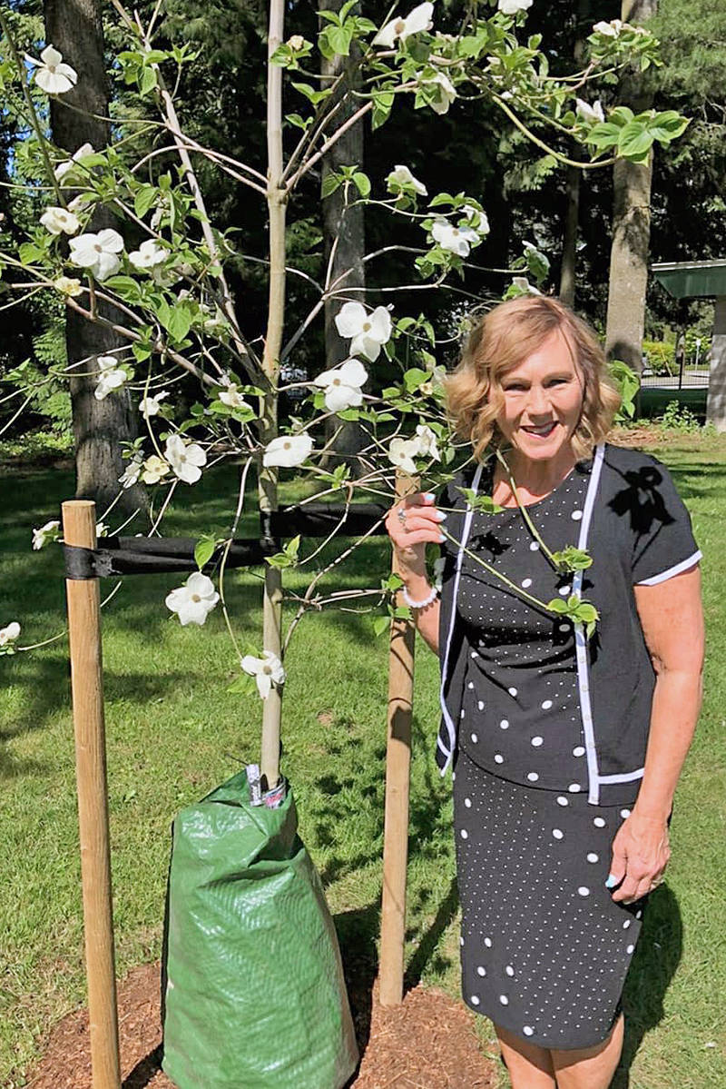 Diane Warawa stands next to the 'Eddie's White Wonder' tree planted in memory of her late husband Mark. It was planted on his birthday, May 7, near his final resting place. (Courtesy Warawa family)