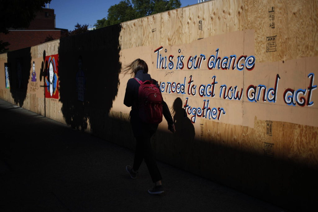 A woman walks by a mural depicting quotes from Provincial Health Officer Dr. Bonnie Henry and Chief Public Health Officer Dr. Theresa Tam as well as others created by artist Ian Morris seen along Government St. in Victoria, B.C., on Wednesday May 6, 2020. THE CANADIAN PRESS/Chad Hipolito