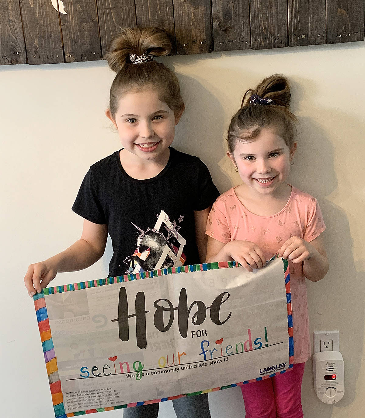 """Seven-year-old Adalynn Susheski, and her five-year-old sister, Natalie, showed off their Hope For poster. They're missing their friends """"big time"""" from James Kennedy Elementary and hoping to see them again soon, explained their mother, Kim. (Kim Susheski/Special to the Langley Advance Times)"""
